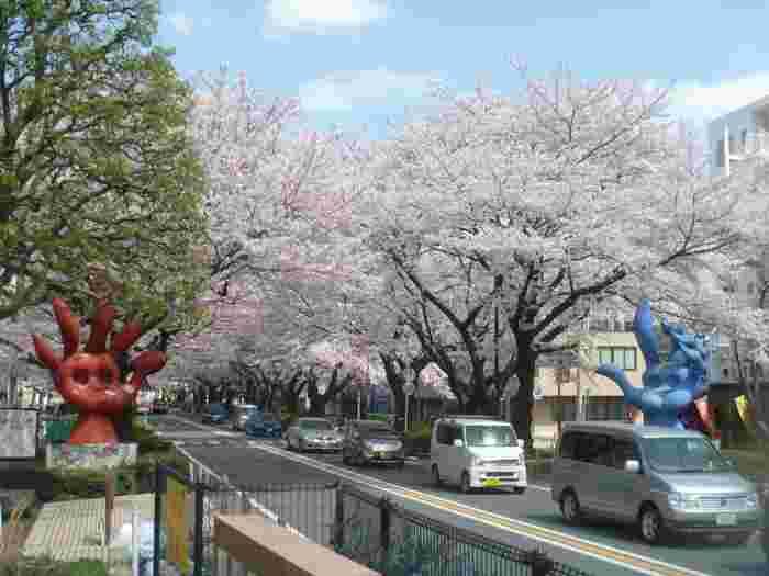 道路を挟んで赤い手と青い手の2つのオブジェが設置されています。