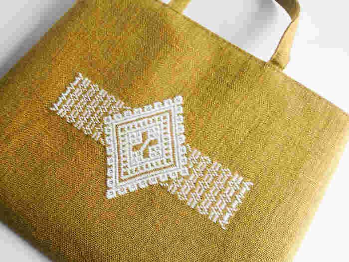 """農家の女性達の""""知恵と工夫""""から生まれたこぎん刺し。津軽地方では野良着のことを「こぎん」と呼んでいたため、この名前がついたそうです。伝統的なこぎん刺しは「藍染の麻布に白い木綿糸」が特徴。現在は様々な布や糸が使われ、現代風にアレンジされた図柄も増えてきています。  ※画像は当記事のために撮影"""