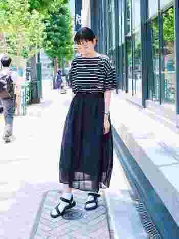 黒のボリュームスカートも、透け感のある素材なら重たくなりません。ボーダーの袖にもチュールが施されているので、より軽やかな着こなしに。足元はスポーツサンダルでトレンド感をプラスすると◎。クールなブラックをデザインと素材感でナチュラルテイストに仕上げた上級コーデです。