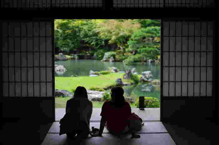 """【「天龍寺」の大方丈前に広がる『曹源池庭園』は、池泉回遊式庭園。池の中央にあるのは、中国の故事になぞらえた""""龍門の滝""""。】"""