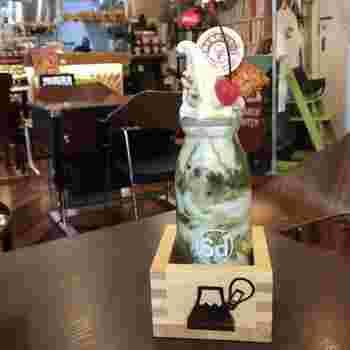 牛乳瓶に盛り付けられた「抹茶めっちゃむっちゃシェイク」は、抹茶やアイス、クリームやあんこなど盛りだくさん。見た目が楽しいメニューやどこか懐かしい店内の雰囲気など、ついつい長居したくなるカフェです。