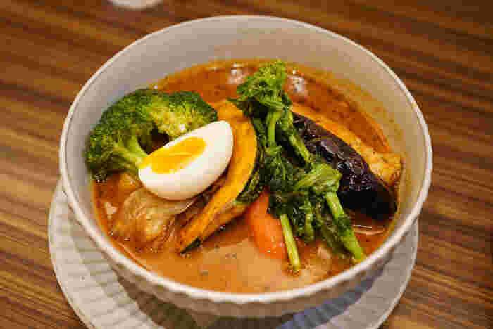 「東京らっきょブラザーズ」は、スープカレーの本場・札幌の名店「スープカレーらっきょ」の東京店。鶏がらや豚骨、お野菜から旨みを引き出したスープは、10時間以上もかけて作るこだわりの味が評判です。多くのメニューが出前館などでデリバリーができますよ。  「季節野菜のスープカレー」は、旬のお野菜2種類のほか、なすやかぼちゃ、ブロッコリーやじゃがいも、たまごが入って具だくさん。食べ応えがあるので、晩ごはんにも良さそう。