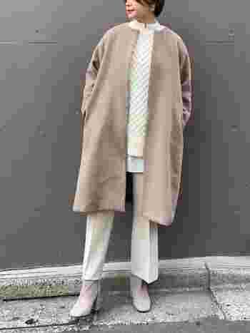 ブラウン系のノーカラーコートに、白のニットとアイボリー系のワイドパンツを合わせたコーディネートです。コートの中は柔らかなカラーで揃えて、暖かみのあるナチュラルフェミニンコーデにまとめています。