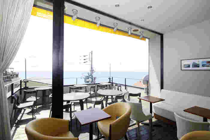 店内は白と黄色を基調とした地中海風インテリア。海を間近に見渡すことが出来るテラス席もあります。