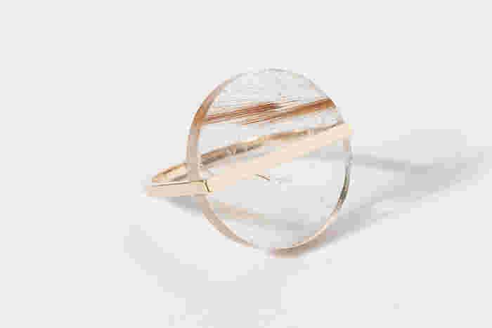 金糸をさしこんだクォーツをカットしたリング。クリアな質感と金属の存在感のコントラストはシンプルながら、遊び心のあ るデザインです。