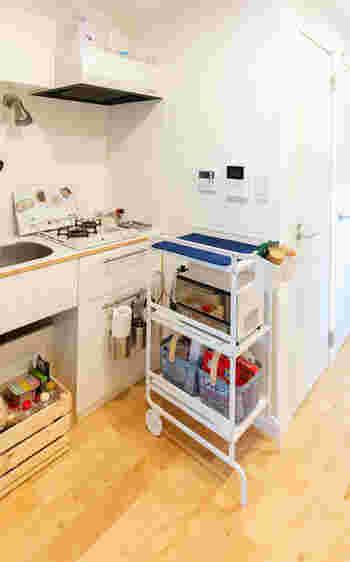スペースの問題はキッチン横に可動式ワゴンを投入し解決。上のトレイに水切りシートを置いて洗い物の水切り場として活用されているのだそう。 家電製品や食料品のストックもきれいに収まっています。