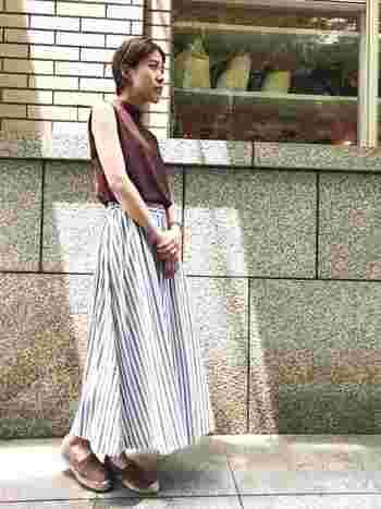 クールな印象のストライプ柄スカート。タイプライター素材で肌ざわりがよいのも魅力です。他のアイテムはブラウンでまとめて、秋を先取り。