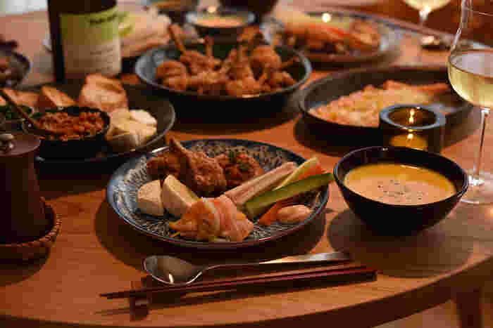 """取り分け用のお皿は20cmくらいのプレート1枚。""""ワンプレートごはん""""にして楽しんでみてはいかがでしょうか?ワインやシャンパンなども並ぶテーブル。多くの食器で溢れてしまわない工夫にも繋がりそう。冨田さんは唯一の柄物を選んでアクセントに。アジアンチックな雰囲気の花柄が描かれたロールストランドの『Ostindia Floris』が、まさにクリスマスのテーブルを華やかにしてくれています。"""