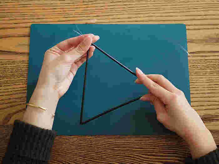 ②ストローの穴に紐を通して三角形を作ったら、頂点を結ぶなどして留めていきます。