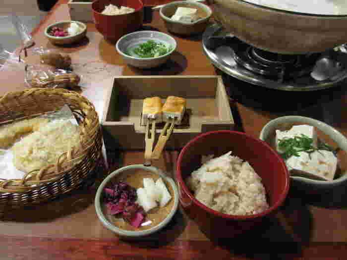 「順正」も、『湯どうふ』とともに、天ぷらや田楽、胡麻豆腐、煮物椀等など、多彩な味わいが楽しめます。【湯どうふに、自家製豆乳や野菜の天麩羅、味噌田楽や炊き込みご飯が付いたコース料理。袋に入っているのは、デザートのカステラ。】