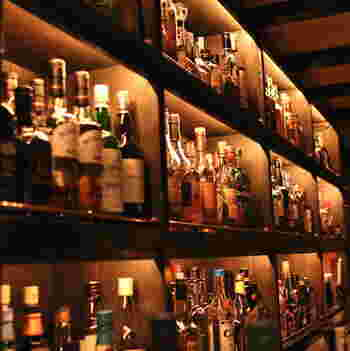 全15席の小さな店内は、重厚なブラウンが基調の落ち着いた空間。ライトに照らされた無数のボトルがムードを演出。