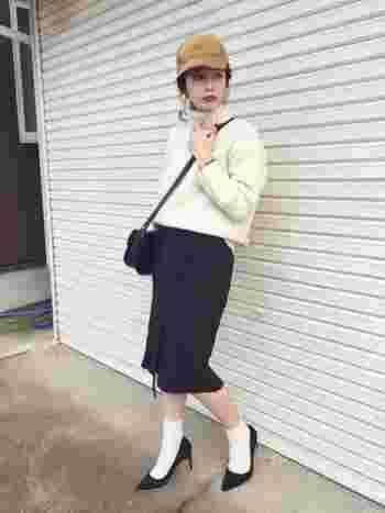 黒の巻きタイトスカートには、ホワイトの靴下×ヒールパンプスできれいめなコーディネートに。下半身を細めのシルエットで仕上げた時は、ボリューミーなトップスでバランスを。キャップで合わせて程よく外すと◎!