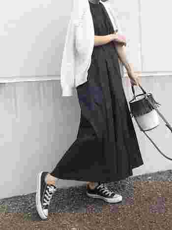 黒のロングワンピースに、カーディガンを合わせたコーデ。カーディガンの白を選べば、ロング丈のワンピースも重くなりません。スニーカーとバッグのカラーを服と合わせることで、すっきりとした印象です。バッグのフリンジがアクセントに。