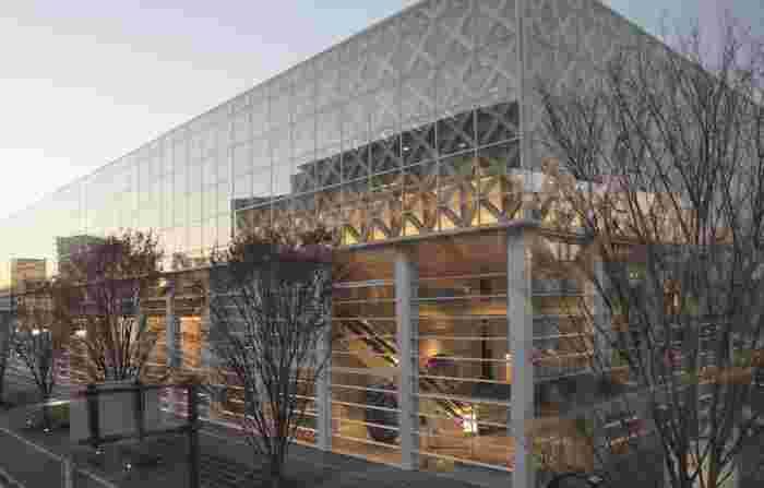 """2015年に開館した「大分県立美術館」は、""""出会いと五感のミュージアム""""をコンセプトに、大分の近世美術や近代日本画など約5,000点のコレクションを所蔵・展示しています。世界的建築家・坂 茂(ばん しげる)さんがデザインを手掛けており、ガラス張りと竹細工のような木組が印象的。"""