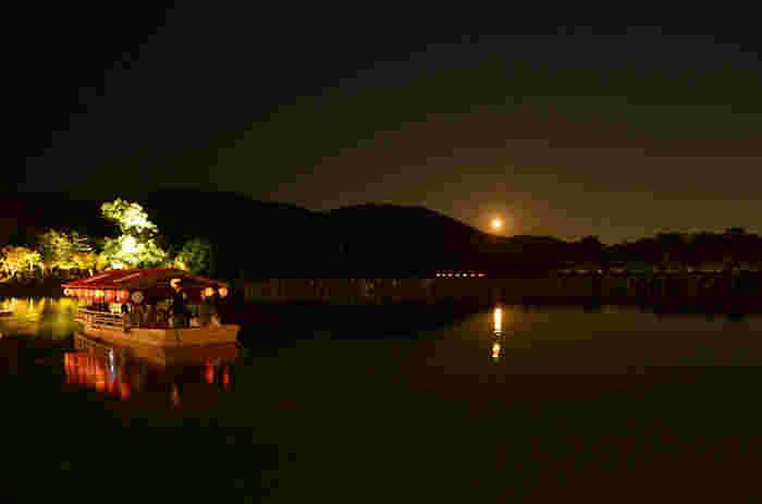 """闇に浮かぶ、煌々とした天空の月と、湖面に映る二つの月。毎年9月15日の中秋から3日間、ここ大沢池では『観月の夕べ』が行われ、貴族のような舟遊びが出来ます。 【画像は「観月の夕べ」の""""満月法会""""。】"""