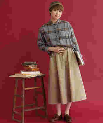 ゆったりシルエットが特徴のチェック柄シャツは、ベージュのロングスカートにタックインした着こなしで。帽子やローファーで秋らしさを演出した、カジュアルガーリーなコーディネートです。