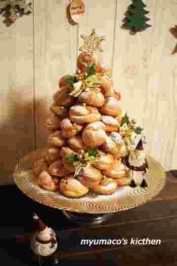 クリスマスムードたっぷりのこちらのクロカンブッシュ。すこし大きなクロカンブッシュを作るときは、中に円錐状のオーブンシートなどを入れて組み立てていくときれいに出来上がります。直径が合うコップなどを中に入れ、そこにオーブンシートを立てるようにすると簡単に芯ができますね。