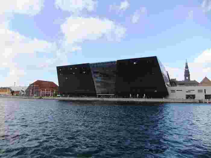 """「デンマーク王立図書館 (Det Kongelige Bibliotek)」は通称""""ブラックダイヤモンド""""と呼ばれており、その名の通り水の都にポツンと宝石箱が浮んでいるよう。外壁に南アフリカ産の黒色花崗岩を用いて設計されており、1999年に新館がオープンしました。"""