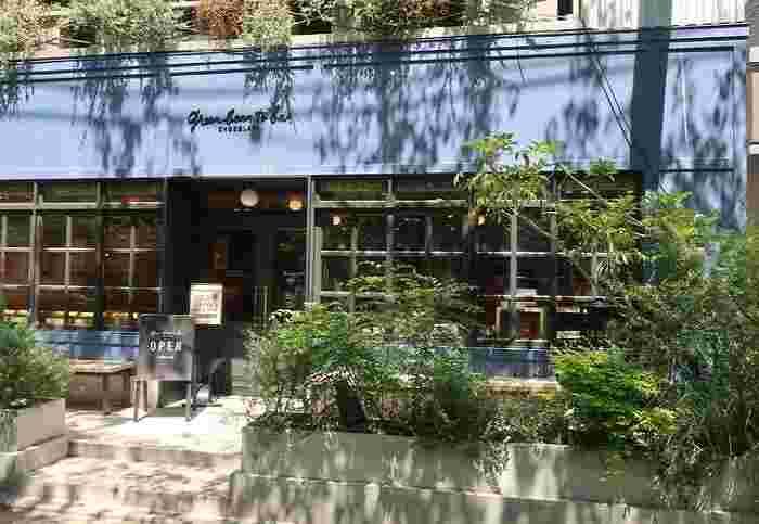 格子窓と並木道に呼応するファサードのグリーンが目印。カフェに併設の工房では、カカオ豆の選別からチョコレート作り、包装まで一連の作業が行われています。