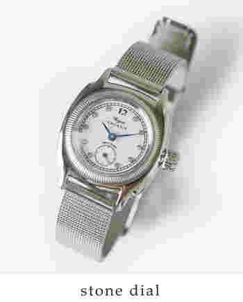 """ブランドやショップのオリジナル時計をプロデュースしてきた実績をもつ「ヨシダトレードカンパニー」のオリジナル時計。シルバーを基調としたメンズライクな雰囲気の中に、文字盤の白×インデックスのクリアストーンによって女性らしさが加わっています。黒で描かれたナンバー""""12""""が印象的です。"""