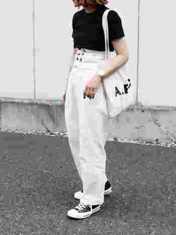 肩からかけた「A.P.C(アーペーセー)」の白のトートバッグ。トップスの黒Tシャツに肩からアクセントを加え、白のボトムスに馴染ませています。