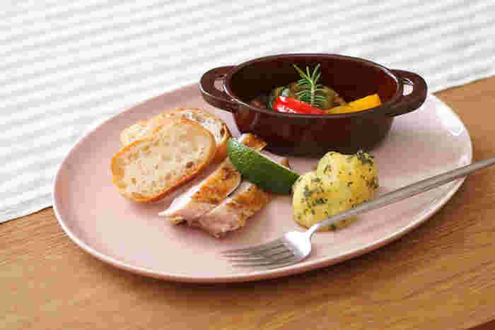 """絵の具のパレットから名づけられた、""""STUDIO M'(スタジオエム)""""のパレットシリーズは、絵の具のような瑞々しい色味が食卓を爽やかに彩ります。 よく見ると、器にちらりとのぞく白い斑模様が、一般的な色釉とはひと味違ったニュアンスをプラスしてくれます。 28cmのオーバルプレートは、何気ないお料理をサッと盛り付けるだけで、なんだかサマになります。薄手でシンプルな形なので、サラダやパスタを盛り付けたり、例えばバーニャカウダ用の野菜を並べたりするのにもぴったり!お料理のジャンルを問わず活躍してくれる器です。また、プレートに小さなボウルやマグをのせれば、お洒落なワンプレートに…。"""