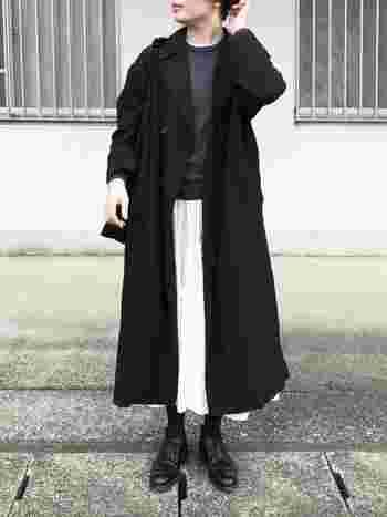 大人のワードローブ1枚あると便利なクルーネックのニットは、カジュアルにもきれいめにも着まわせる心強いアイテム。こちらのコーディネートでは、ニットやアウター、バッグ、靴などを黒っぽいアイテムでまとめ、白のスカートポイントにしています。首元からチラリと見せた白のインナーも、さりげないアクセントになっていて素敵ですね。