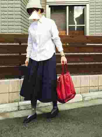 白シャツに濃紺のタックスカートを合わせたシンプルなモノトーンコーディネートに、赤のトートバッグと柄ハイソックスをプラス。上品でさわやかなコーディネートに仕上がっています。
