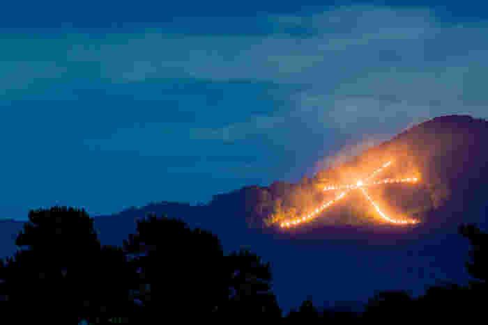 祇園祭と共に、京都の夏の風物詩として知られている「五山の送り火」。大文字焼と呼ばれることもありますが、正確には、お盆にご先祖様をお送りする由緒正しい習わしです。京都を囲む5つの山に、『大』『妙法』『船形』『鳥居形』、左大文字と呼ばれるもう一つの『大』の字が、京都の夜を灯します。