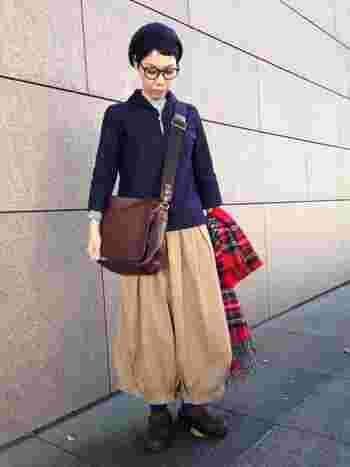ふんわりパンツにレザーのクロスバッグという、ボーイッシュな着こなし。真っ赤なチェックのストールを添えるだけで、たちまち女性らしさが漂います。