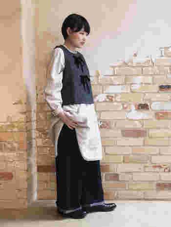 厚みのあるリネン素材で、レイヤードにもぴったりな白のチュニックは、前後で着丈が違うなどの細かいディテールが魅力的なアイテム。グレーのベストとワイドパンツを合わせた、ナチュラルとマニッシュのミックススタイルコーデです。