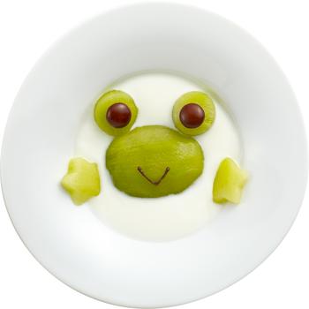 大きなカエルがお皿からこんにちは! キウイの刺激が苦手な子どもでも、ヨーグルトと混ぜることでまろやかになり、食べやすくなります。  【材料】 ・明治ブルガリアヨーグルトLB81プレーン 60g ・キウイフルーツ 1個 ・マーブルチョコレート(茶) 2個 ・チョコペン 適量  【作り方】 ①キウイフルーツの皮をむき、タテに半分に切ります。半分はそのままに、残りの半分から丸い目を2つ、手(花型)を2つつくります。 ②プレーンヨーグルトをお皿またはボウルに入れます。 ③半分に切ったキウイフルーツを中心に置き、先程カットした目と手をのせます。 ④マーブルチョコレートの目玉をのせて、チョコペンで口を描きます。