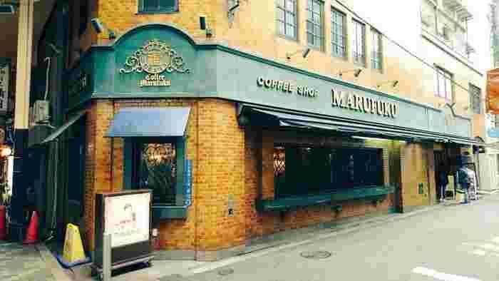 1939年創業の老舗喫茶店「丸福珈琲店」。レトロなレンガ壁の外装におしゃれな看板が素敵です。