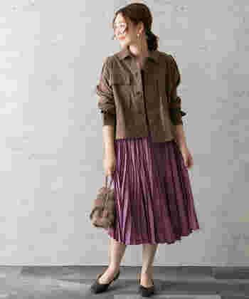 サテン素材のプリーツスカートに、ブラウンのシャツを合わせたコーディネートです。全体を秋カラーでまとめて、トレンド感抜群なスタイリングに仕上げています。腕をまくって手首を見せることで、ボリューム感のあるアイテムを着ても着ぶくれして見えません。