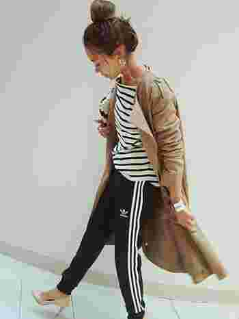 adidasのジャージパンツとボーダーTシャツのコーデに、ベージュのコートとヒールのパンプスで女性らしく着こなしたスタイル。トップスとボトムスのラインをリンクさせるテクニックも◎
