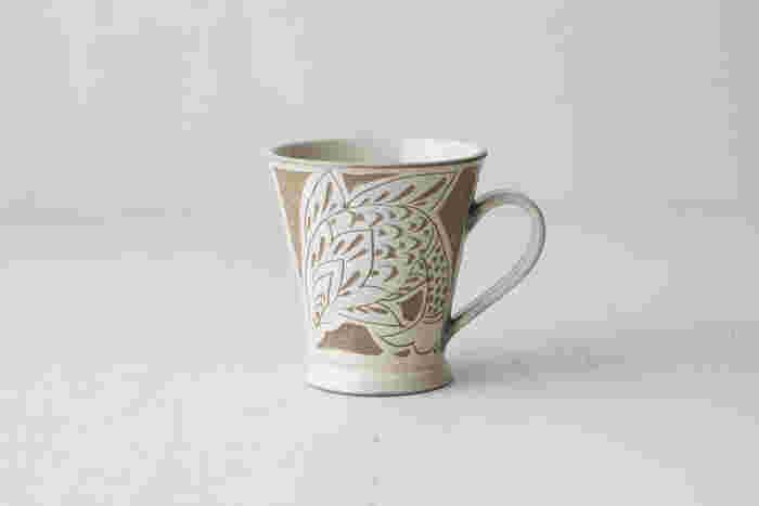 沖縄県の伝統工芸「やちむん」は自然をモチーフにした大胆な絵柄と、南国らしい色鮮やかな絵付けが特徴です。やちむんも小鹿田焼や小石原焼と同じく、民藝の器として高く評価されている伝統的な焼き物です。こちらは300年以上続く老舗の窯元、「育陶園(いくとうえん)」の素敵なマグカップ。伝統的な線彫の技法を用いた魚紋線彫シリーズの器は、繊細かつリズミカルな美しい絵柄が特徴です。