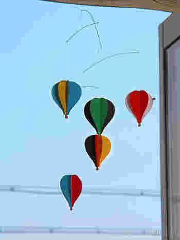 お部屋の中をぷかぷか浮かぶ、カラフルな気球たち。窓越しに見える空と重なると、本当の気球を眺めているかのような気分に。