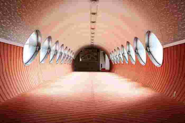 渡り廊下を進むと、妙に近未来的なデザインにびっくり。レトロなカーペットが廊下の下半分を占め、めがねのような形の窓がずらっと並んでいます。左右対称の不思議な空間は、まるで宇宙船の中のよう。いろんな角度から写真を撮りたくなります。