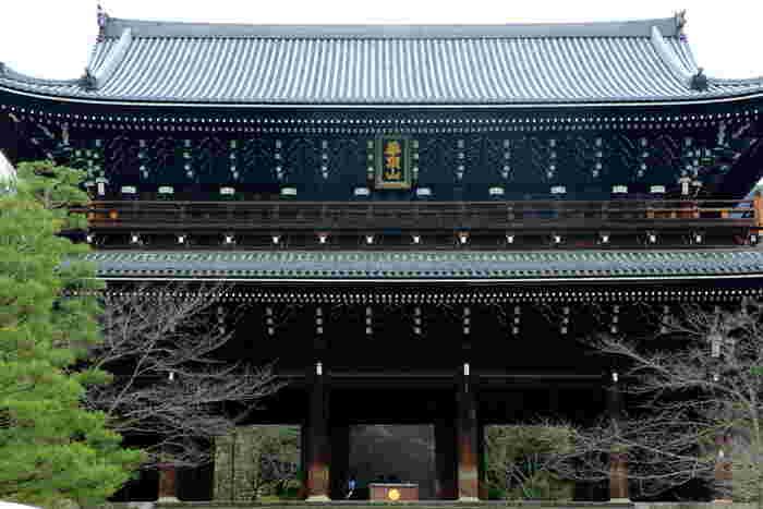 """「青蓮院」の南側、円山公園の北部一帯を占める浄土宗の総本山「知恩院」。日本最大を誇る荘厳な木造門が印象的な大寺院です。  「知恩院」は、浄土宗の元祖・法然上人が布教し、入滅した地。境内は、3つのエリアからなり、三門と塔頭がある下段、御影堂などの伽藍がある中段、勢至堂や御廟がある上段に分けられます。上段は、開創当初の寺域で、中下段の伽藍の数々は江戸期に幕府の援助によって造営されたものです。  「知恩院」の見所は、何と言っても""""京都三大門""""に数えられる国宝の「三門」と、上人の御影を祀る国宝の「御影堂」です。 (★「御影堂」は、平成30年度末まで大規模修繕工事中です)  他に「大鐘楼」や、境内上方にある知恩院最古の建物「勢至堂」も時間があったら、ぜひ訪れて欲しいスポットです。 【1月末頃の「知恩院」三門】"""