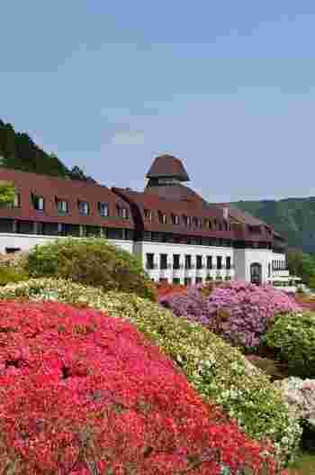 """箱根神社のほど近くの高台にある「小田急山のホテル」は、三菱の創業者、岩崎彌太郎の甥である岩崎小彌太男爵の別邸が建てられていた場所にあるホテルです。火災や震災による建て替えを経て、現在の赤い屋根に白い壁の建物に。スイス・レマン湖のほとりに建つ古城をイメージしているそう。30種3,000株のツツジが咲き誇る庭園から""""花のホテル""""とも呼ばれ、多くの方に親しまれています。"""