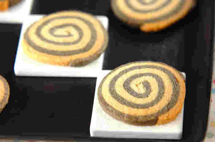 くるくるかわいいうずまき模様の作り方は意外と簡単♪2種類の色違いの生地を1cm位ずらして重ね、くるくる巻いていくだけ。こちらのレシピはそれぞれの生地に練り黒ゴマ、練り白ゴマを混ぜて作ったくるくるクッキー。一見すると、チョコクッキーに見えますが、食べてびっくり!栄養も満点のゴマクッキー是非お試しあれ!