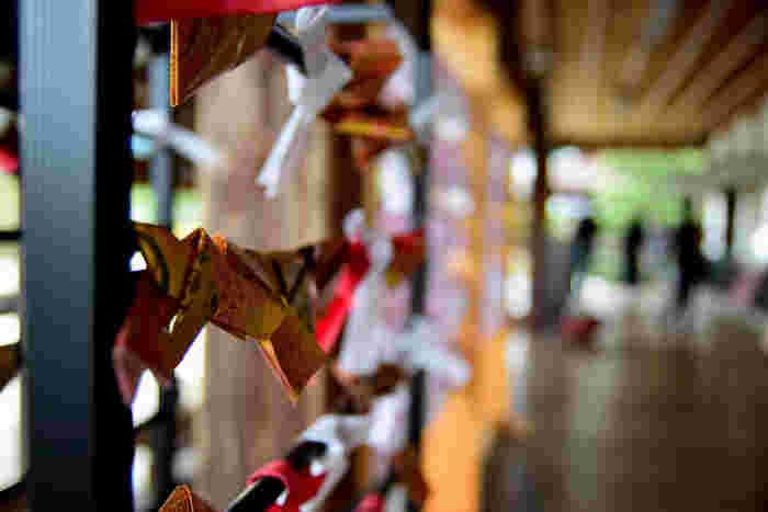 本堂「五大堂」のお守り授与所では、黒檀の木札に本尊の不動明王が彫られた「不動明王守り」や、季節の花々があしらわれた「花守り」等など様々なお守りが扱われています。せっかく嵯峨野を訪れたのなら、旅の記念にお守りを授かりましょう。  【画像は、『源氏物語』風の「縁結びお守り」と、おみくじ。『源氏物語』のモデルは、嵯峨天皇の皇子である源融(みなもとのとおる)です。】  大覚寺の雅で華麗な「女みくじ」。千代紙風のおみくじの中には、ストラップの「一言守り」が入っています。