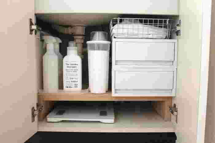 収納場所に困るヘルスメーターは、洗面シンクの下に木の台をつくってそこに隙間収納。木の台の上には、洗剤や掃除用品などを保管して。