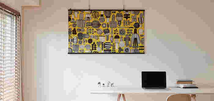 """こちらは「marimekko(マリメッコ)」の""""最高の庭師""""という意味を持つデザインの布地を、オーダータペストリーに仕上げたものです。色鮮やかな黄色ベースのタペストリーを白い壁のセンターに配置するだけで、空間の雰囲気がグッと華やぎますね。"""
