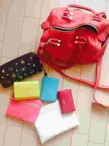 鮮やかな赤のバッグの中にはさらに鮮やかな彩りが広がり、財布やポーチなどが同じブランドのアイテムで統一されています。華やかな女性を思わせるコーディネートに仕上がっていますね。