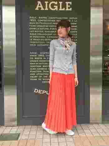 ライトグレーのカーディガンは蛍光カラーとの相性も◎シルエットが美しいオレンジ色のロングプリーツスカートを合わせて、上品にまとめたスタイルです。