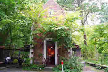 木々の中に佇む、赤いレンガ造りの一軒家。フランスの田舎をイメージしたカフェです。