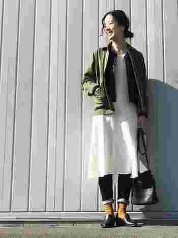 白のワンピースという一見涼しそうなアイテムも、インナーダウンやデニムとの重ね着で暖かく着こなしたスタイルです。