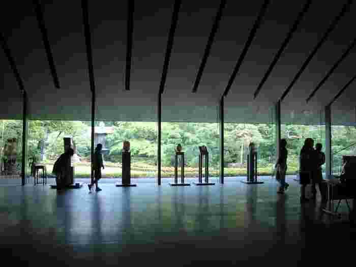 広々としたホールには根津嘉一郎氏のコレクションが展示されています。展示の先には、美しい日本庭園がガラス越しに広がっています。