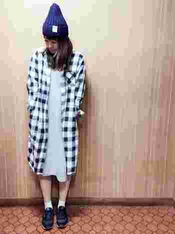 印象的な大きめギンガムチェック柄のロングシャツを使ったコーディネート。  インナーをワンピースにすることで女の子らしさを演出しています。 ハイテクスニーカーとニット帽を合わせて、お洒落なスポーツミックススタイルの完成です。